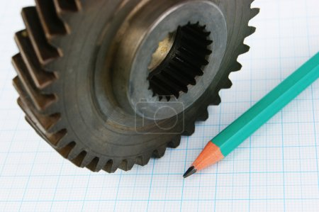 Gear and pencil on graph paper