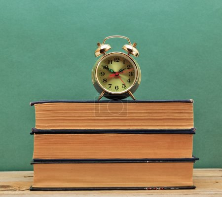 Old books and alarm clock