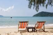 Two beach chairs on beach.