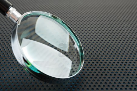 Magnifying glass on a metallic background