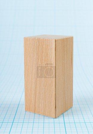 Photo pour Parallélépipède en bois forme géométrique sur papier millimétré - image libre de droit