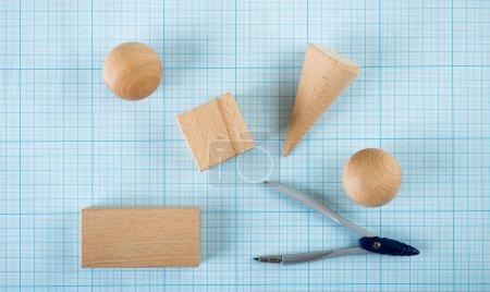 Photo pour Formes géométriques en bois sur papier millimétré - image libre de droit