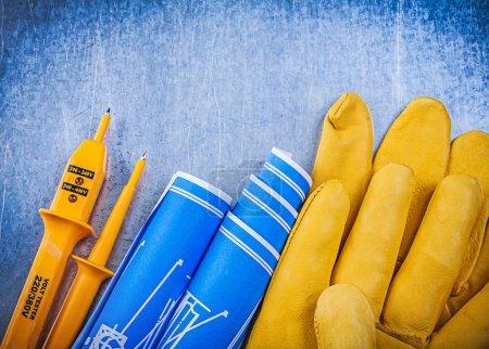 Photo pour Gants de sécurité testeur électrique jaune dessins techniques bleus sur fond métallique . - image libre de droit