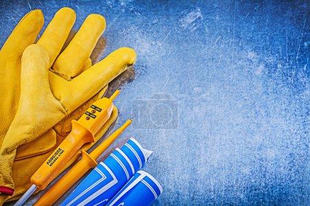 Photo pour Gants de sécurité testeur électrique jaune bleu bleus sur fond métallique - image libre de droit