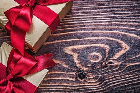 Photo pour Boîtes cadeaux enveloppées avec rubans de satin rouge sur panneau de bois . - image libre de droit