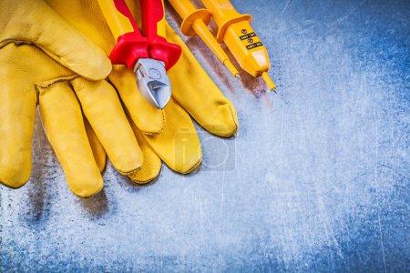 Photo pour Testeur électrique jaune, gants de sécurité et pinces coupantes sur fond métallique concept électricité . - image libre de droit