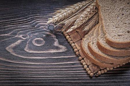 Ripe rye wheat ears and sliced brown bread on wick...