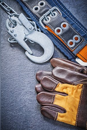 Foto de Guantes de cuero en concepto de mantenimiento de fondo negro y cinturón de seguridad de construcción - Imagen libre de derechos
