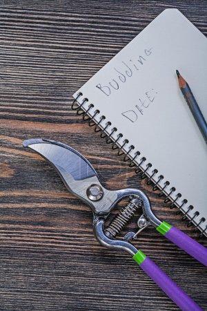 Notepad, pencil and garden pruner