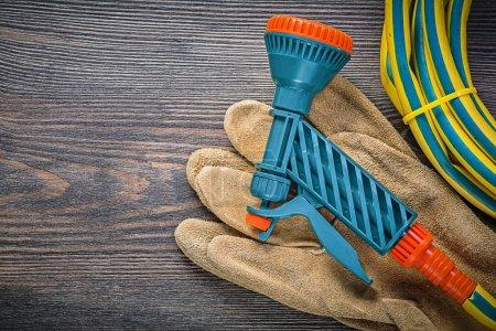 Garden rubber hose water sprinkler safety gloves on wooden board