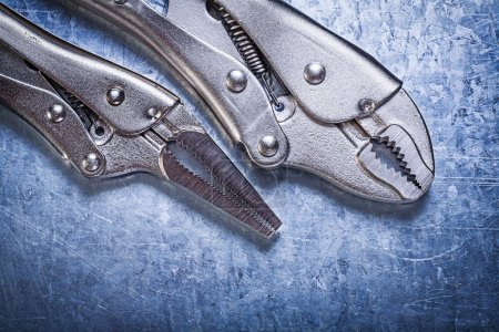 Lock jaw pliers on metallic background construction concept