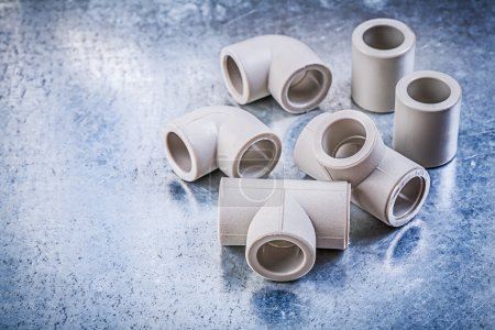Plastic pipe fittings on metallic surface construction concept