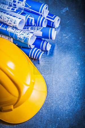 Photo for Blue construction drawings yellow building helmet on scratched metallic background. - Royalty Free Image