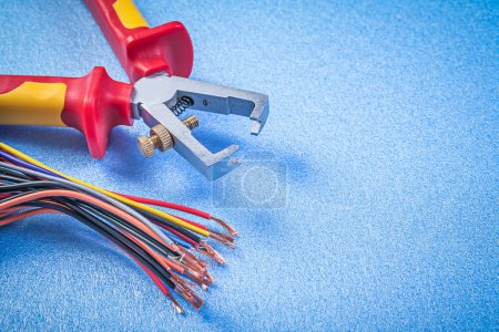 Photo for Insulated wire strippers electric cables on blue background electricity concept. - Royalty Free Image