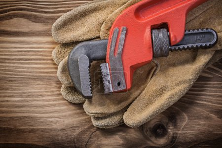 Photo for Pair of leather protective gloves pipe wrench on wooden board construction concept. - Royalty Free Image