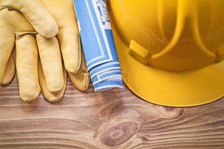 Blue blueprint hard hat safety gloves on wood board construction