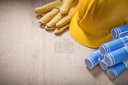 Blue construction plans hard hat safety gloves on wooden board