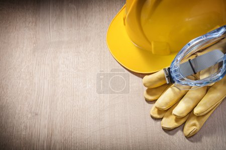 Composition of hard hat safety gloves spectacles on wooden board