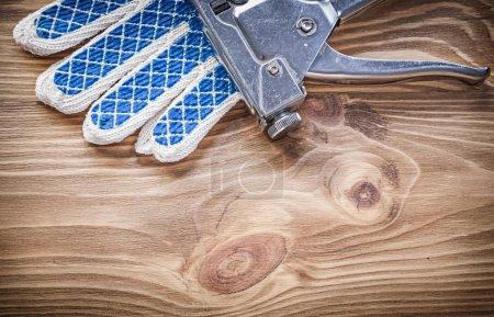 Composition of stapler gun safety gloves on wooden board