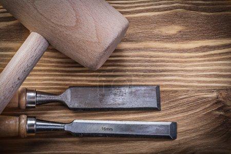 Lump hammer firmer chisels on vintage wooden board construction