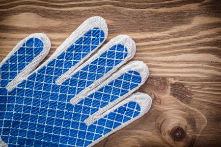 Pair of protective gloves on wooden board construction concept