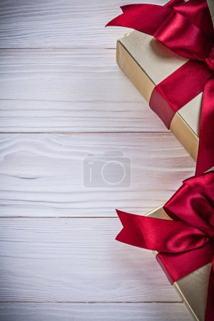 Gift-containers with tied ribbons on wooden board holidays conce