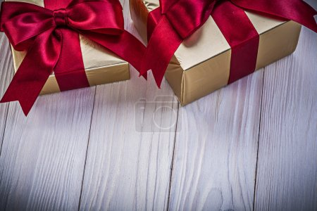 Golden gift boxes with red tapes on wooden board holidays concep