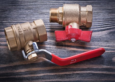 Brass gate lever ball valves on wooden background plumbing conce