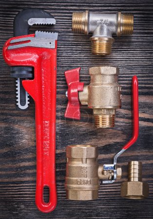 Composition of monkey wrench brass fittings water valve on woode