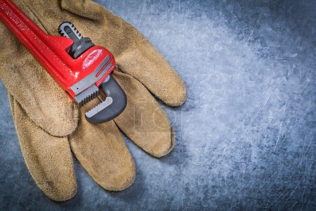 Monkey wrench protective gloves on scratched metallic background
