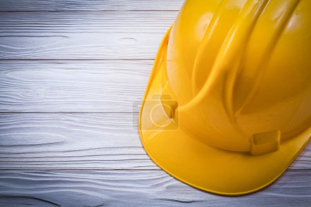 Protective hard hat on wooden board construction concept