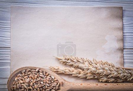 Photo pour Blé seigle épis de maïs cuillère en bois vintage papier sur planche de bois nourriture et boisson concept . - image libre de droit