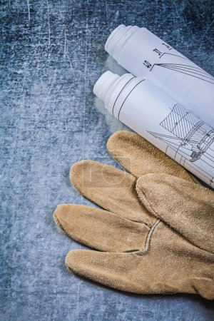 Rolled construction drawings leather safety gloves on metallic b