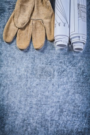 Rolled blueprints leather safety gloves on metallic background c