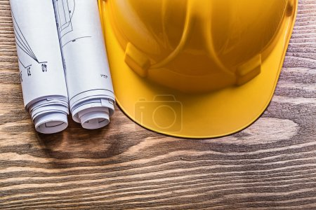 Rolled construction drawings hard hat on wooden board maintenanc