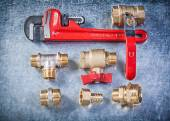Collection of plumbing brassware on metallic background directly