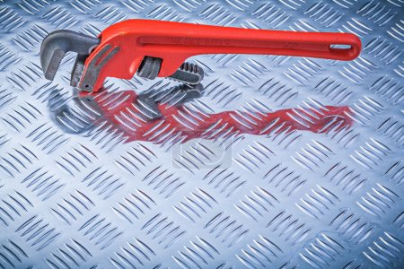 Metal pipe wrench on corrugated metallic background directly abo