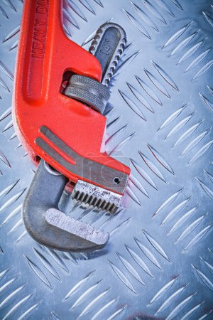 Red adjustable monkey wrench on corrugated metallic background c
