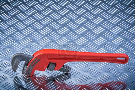 Metal pipe wrench on corrugated metallic plate maintenance conce
