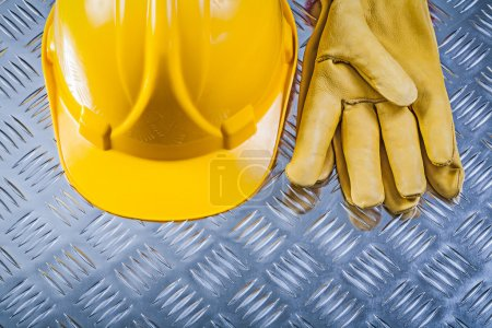 Protective leather gloves hard hat on corrugated metal backgroun