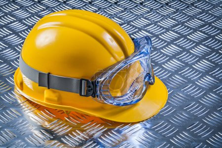 Safety goggles hard hat on fluted metal plate construction conce
