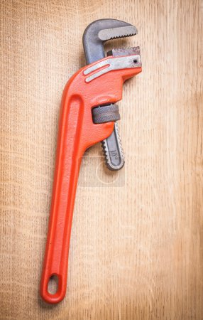 Pipe wrench on wooden board