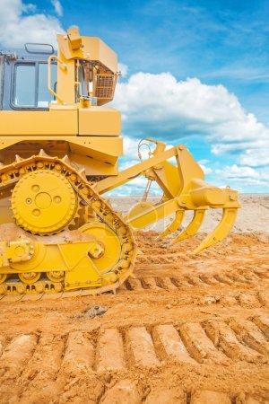 Photo pour Camion bulldozer travaillant sur le sable sur le ciel de fond - image libre de droit