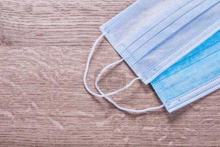 Photo pour Medical surgical flu ilness protective face masks textile filter on wooden table - image libre de droit