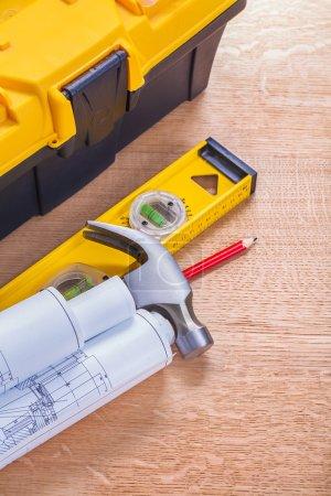 Rolled blueprints, hammer, level
