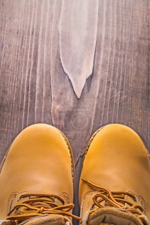 View of working boots on wooden board