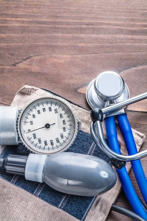 Photo for Stethoscope and blood pressure monitor on vintage wooden board with copyspace medical comcept - Royalty Free Image