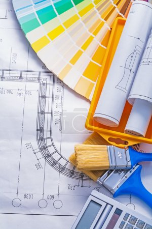 Paintbrushes, calculator, rolled blueprints