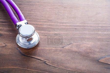 Photo pour Tête du stéthoscope sur une planche en bois vintage avec fond organisés concept médical - image libre de droit