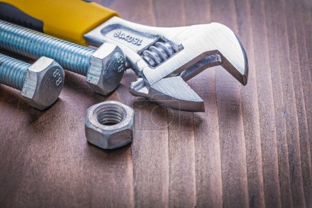 Photo for Composition of adjustable wrench bolts and nut on vintage wooden board construction concept - Royalty Free Image